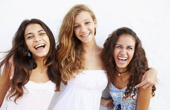 Teen girls smiling with braces